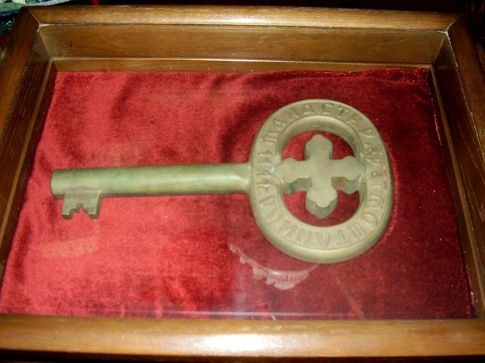 """Кључ из манастира Моштанице на коме се налази натпис """"1111"""", што наводи на претпоставку да манастир потиче из 12. вијека. Сматра се да је ово копија оригиналног кључа која је урађена по сјећању на прави, који је био дрвен и који је изгледа настрадао у неком од многобројних пожара које је манастир претрпио током своје историје."""